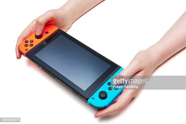 Detail of a woman's hands holding a Nintendo Switch console fitted with a pair of JoyCon controllers taken on February 22 2017