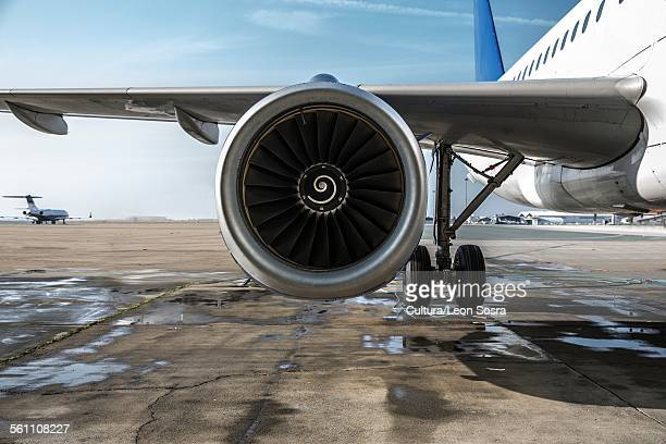 Detail of airplane wing and engine on tarmac at airport