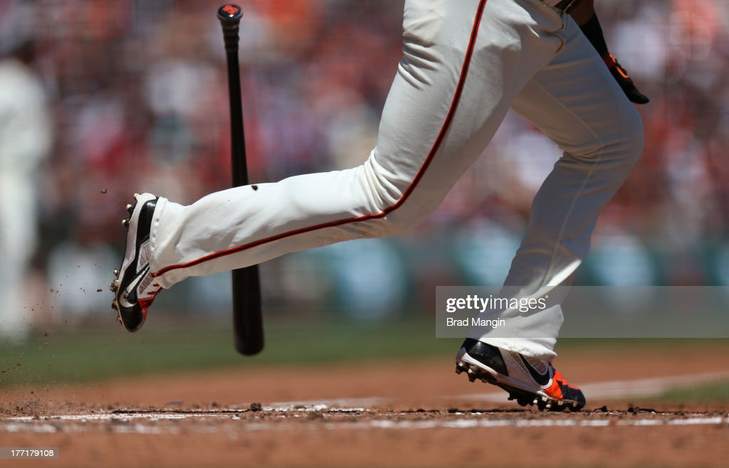 Detail of Andres Torres of the San Francisco Giants running to first base wearing Nike cleats and dropping his bat against the Boston Red Sox during...