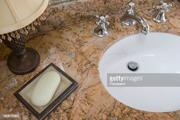 Detail of bathroom sink with chrome faucet and soap dish
