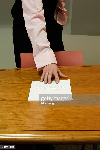 detail of businessman standing behind desk grabbing for confidential document