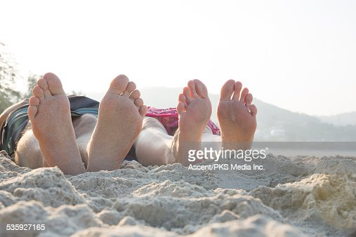 Detail of couple's feet upturned on beach, by sea : Stock Photo