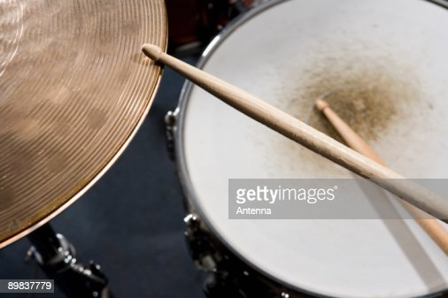 Detail of drumsticks and a drum kit