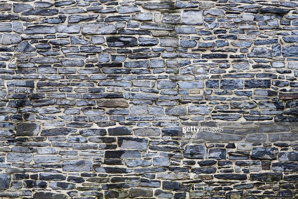 Detail of exterior dark stone wall background stock photo for Exterior background