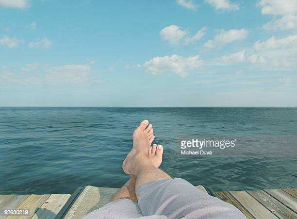 detail of feet relaxing on chair in front of water