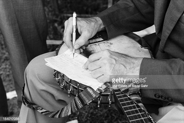 Detail of folk musician and activist Pete Seeger's hands as he drafts a piece of writing atop his banjo across his lap backstage at the Newport Folk...