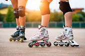 Detail of girls rollerblading with knee pads
