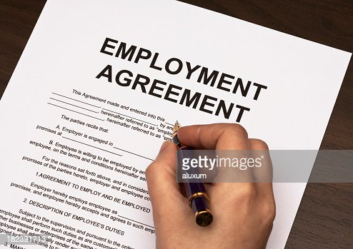 Detail Of Hand Holding Pen Over Employment Agreement Stock Photo