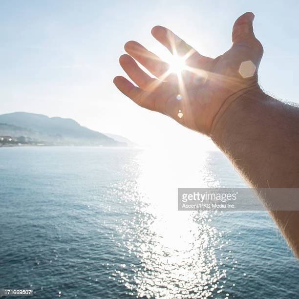 Detail of hand stretched to cup rays of sunrise