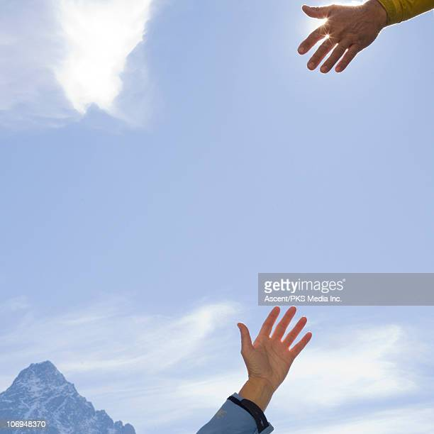 Detail of hands about to grasp, above mountains