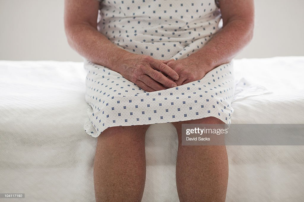 Detail of hands and legs on hospital bed