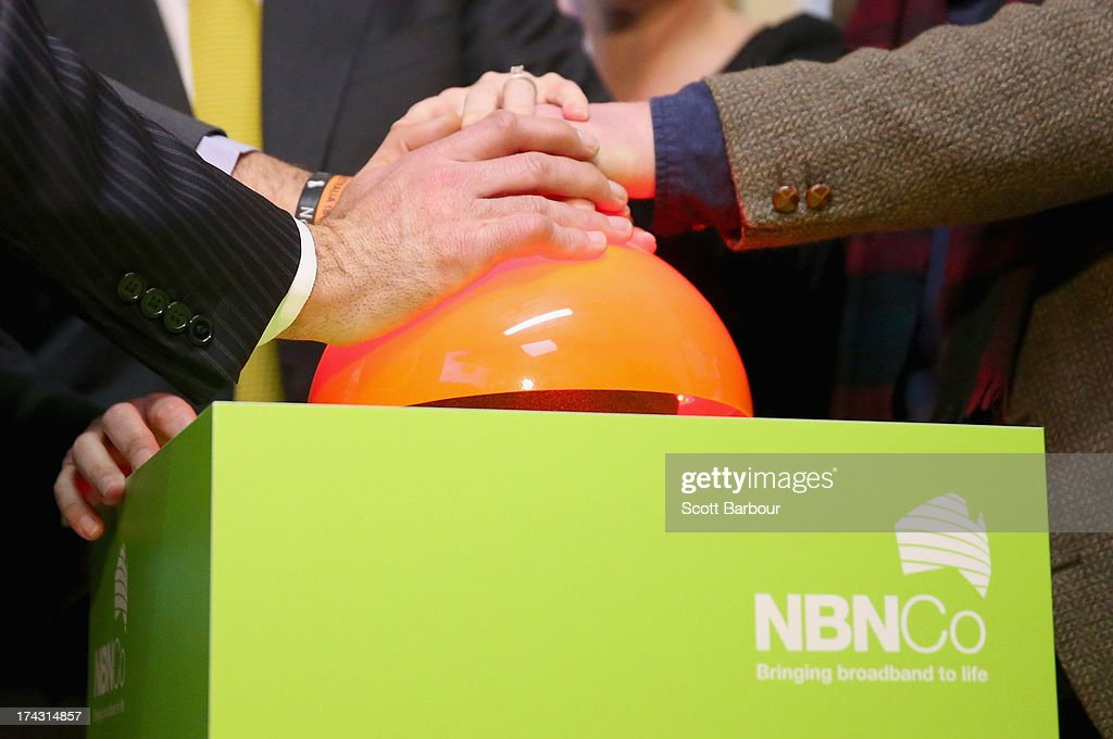 A detail of hands on the button pushed by Anthony Albanese, Deputy Prime Minister of Australia and others to switch on the NBN fibre network to an adtional 2,600 homes and businesses in Brunswick at the Brunswick Digital Hub on July 24, 2013 in Melbourne, Australia. The national broadband network is being rolled out accross Australia, and is to provide over 93% of Australian homes and business with access to a fibre optic network. As the 2013 Australian federal election approaches and infrastructure remains a major concern of voters, the Labor party continues to push the power of their fibre direct to the home plan with the Liberal party pushing what it claims is a more cost-effective plan using existing copper and new optical fibre.