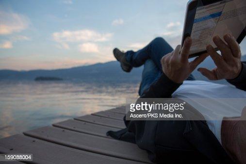 Detail of man using digital tablet on lake wharf : Stock Photo