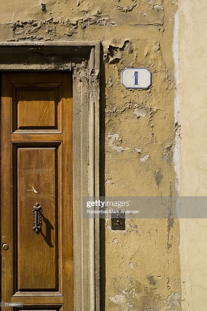 Detail of number one on wall with wooden door : Stock Photo