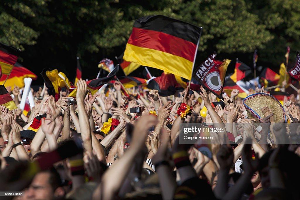 Detail of people in a crowd waving German flags