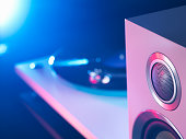 Detail of purple and blue spot lit hi fi speaker and turntable playing a vinyl record
