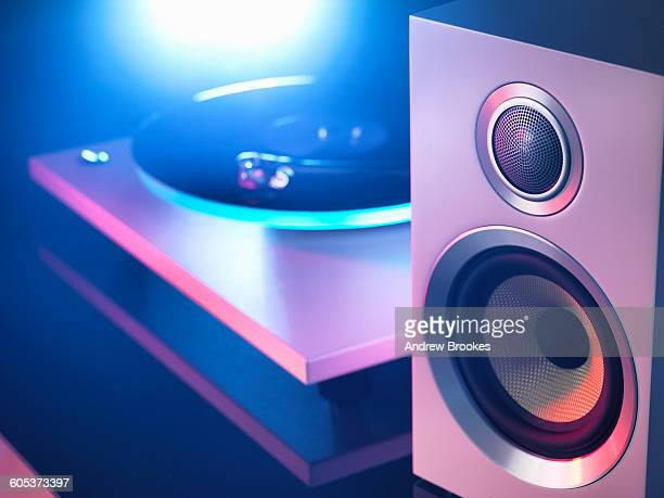 Detail of purple and blue spot lit hi fi speaker with turntable playing a vinyl record