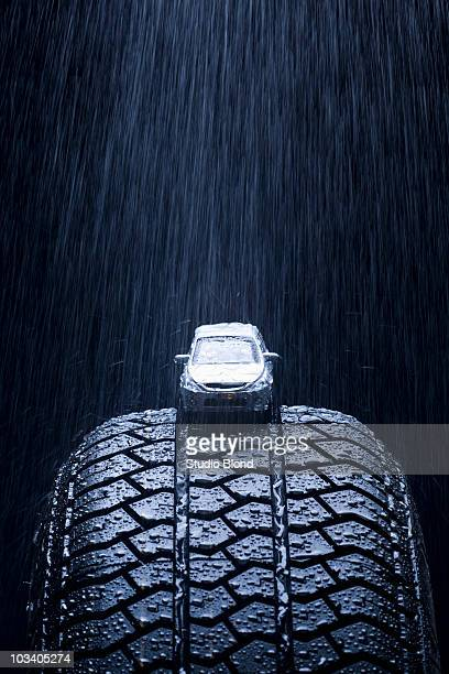 Detail of rain falling on a toy car on a tire