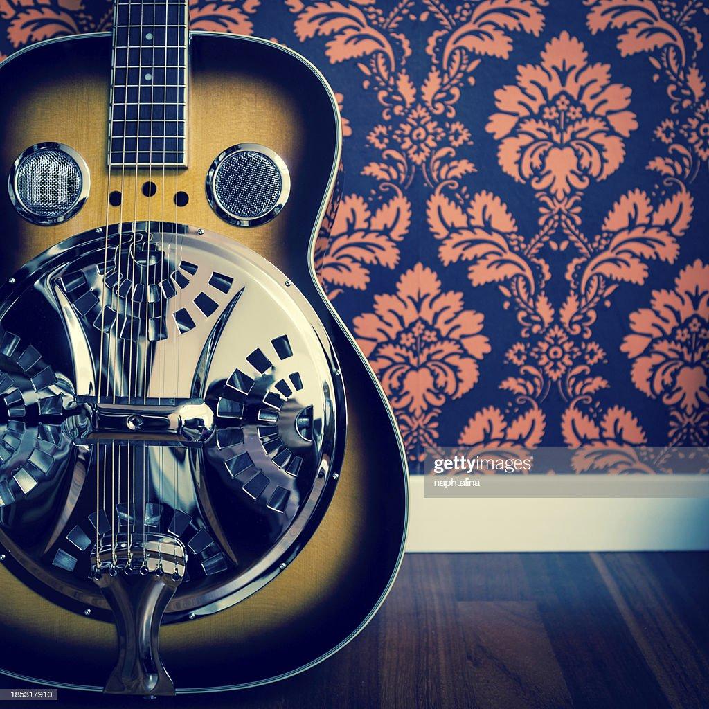 Detail of resonator guitar and damask wall