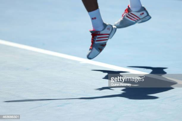 Detail of shadow as Novak Djokovic of Serbia serves in his fourth round match against Fabio Fognini of Italy during day seven of the 2014 Australian...
