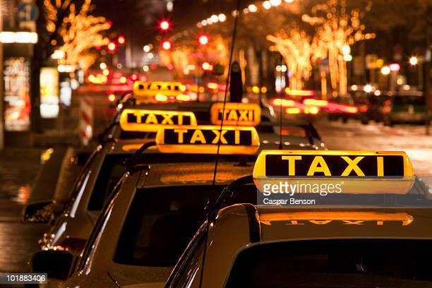 Detail of taxi cabs parked in a row at night