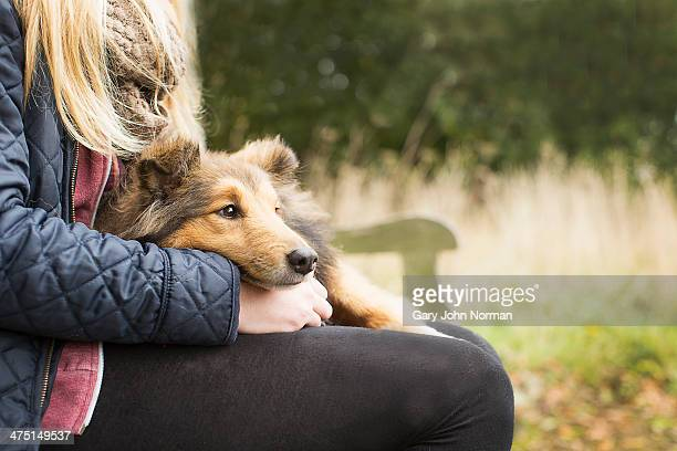 Detail of teenage girl sitting on country bench with dog