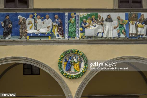 Detail of the ceramic glazed frieze and of the glazed terracotta roundel by Giovanni Della Robbia on the façade of Ospedale del Ceppo