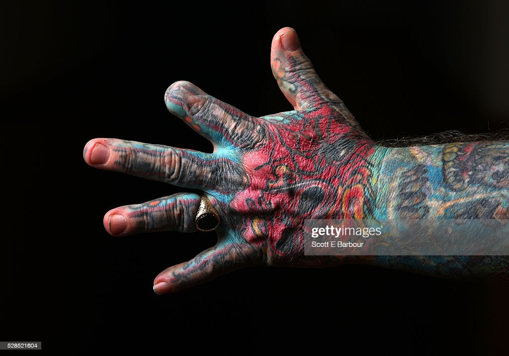 A detail of the hand of John Kenney with a finger cut off as he poses for a portrait in his home on April 28, 2016 in Melbourne, Australia. The 60 year old has tattoos all over his body, including his eyelids and eyeballs. His fascination with tattoos started when he was 18, and led to him contracting Hepatitis C from a dirty needle. He even hacked a finger off with a meat cleaver during a part-time job to claim compensation money. After a life of crime on the streets and drug addiction, John Kenney now speaks to school children about the perils of drug abuse and tattoos and is an advocate for the homeless.