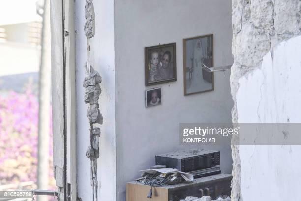 A detail of the remains of the collapsed palace in which you can see photos of the tenants hung on the wall At the early lights of the morning a...