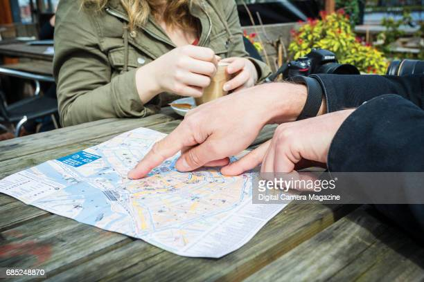 Detail of tourists looking at a city guide map at a cafe in Amsterdam taken on April 19 2016