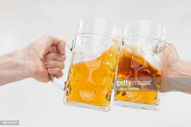 Detail of two people toasting with mugs of beer