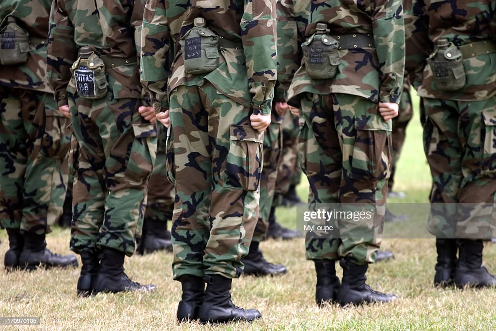 Detail of USAF Basic Trainees group in formation, photo from shoulders to feet while standing in grass field, fatiques and canteens.