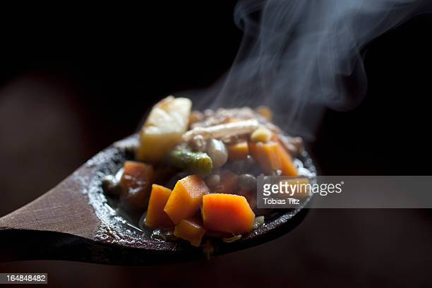 Detail of vegetable stew on a wooden spoon