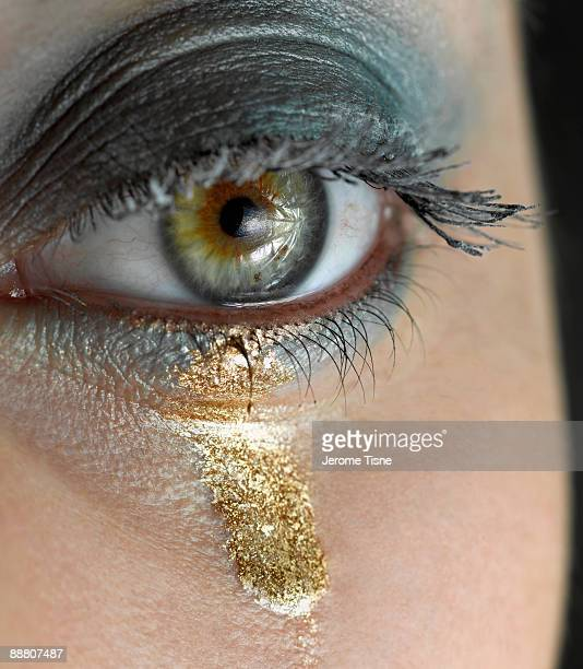 Detail of woman's eye with a gold tear