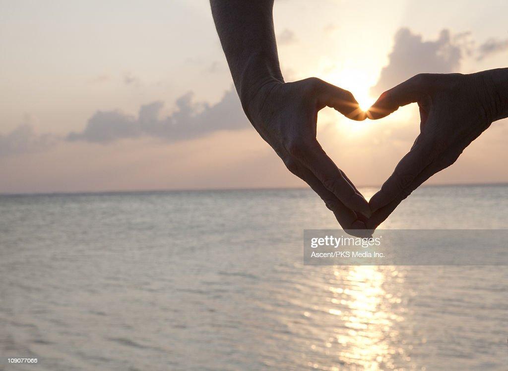 Detail of woman's hands making heart shape, sea : Foto de stock
