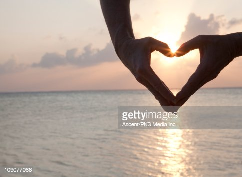 Detail of woman's hands making heart shape, sea : Stock Photo