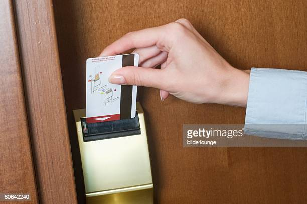 detail of young businesswoman opening door to hotel room with key card