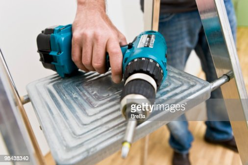 detail of young man putting cordless screwdriver on ladder : Stock Photo