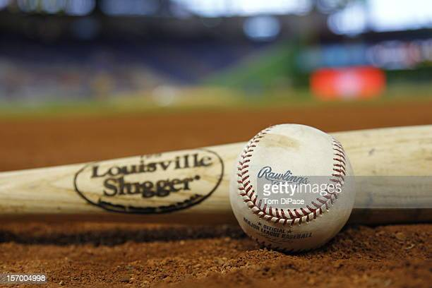 A detail shot of a Louisville Slugger bat and a Rawlings official Major League Baseball is seen on the field before the game between the Milwaukee...