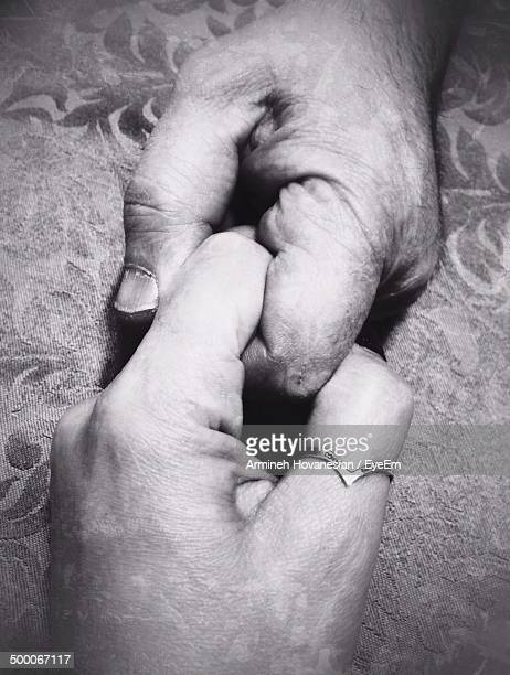 Detail shot of two people holding fingers
