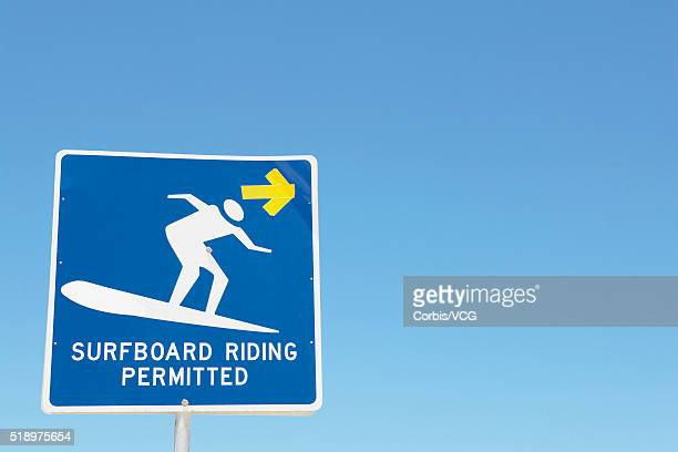 Detail view of a 'Surfboard riding permitted' sign against blue sky