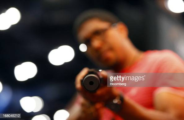 A detail view of the barrel of a Bushmaster gun is seen as an attendee stands for a photograph during the 2013 National Rifle Association Annual...