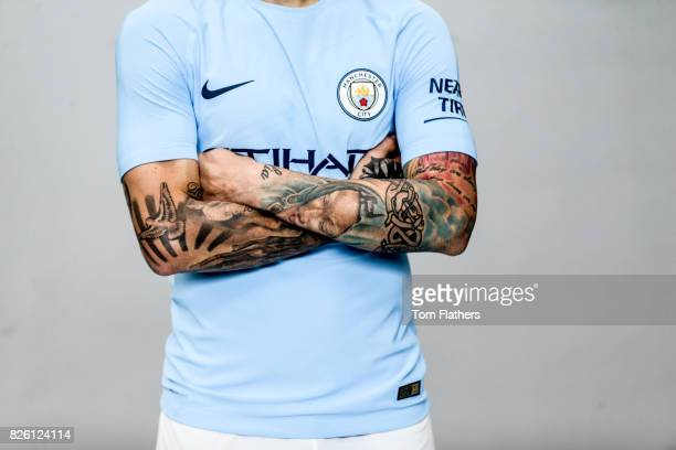 A detail view of the Nike logo Manchester City badge and Nicolas Otamendi's arm tattoos