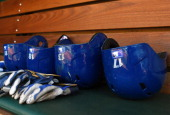 A detailed look of batting helmets and batting gloves belonging to Toronton Blue Jays players sitting on the bench in the dugout prior to the game...