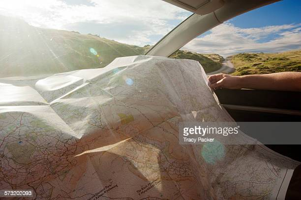 A detailed map is being scrutinised in bright sunshine over the dashboard of a parked car as the driver considers which direction to head over the...