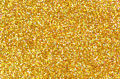 Detailed texture of glittering golden dust surface. High resolution photo.