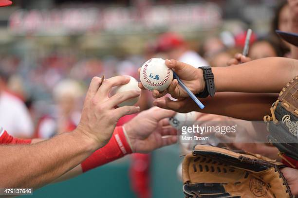A detailed view of a ball bearing the MLB logo being handed by a fan to Mike Trout of the Los Angeles Angels of Anaheim before the game against the...