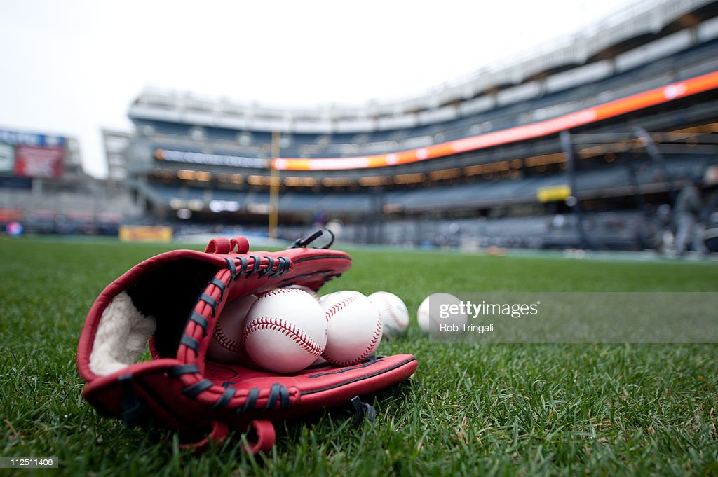 A detailed view of a baseball glove and baseballs laying on the field prior to the game between the Texas Rangers and the New York Yankees on...
