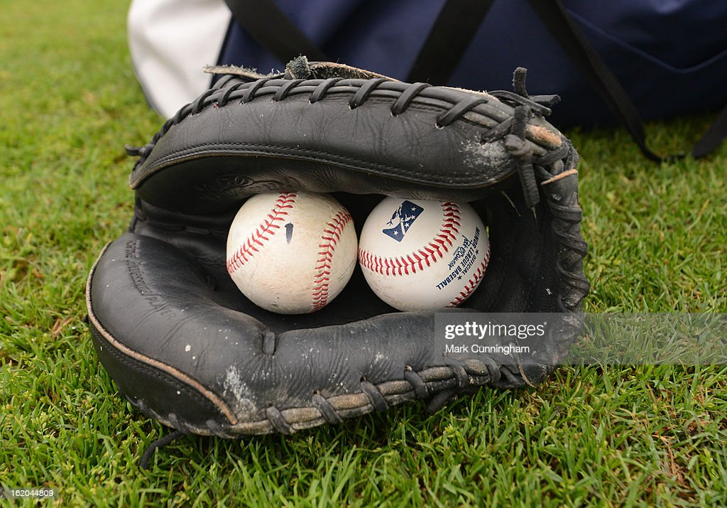 A detailed view of a catchers glove and baseballs laying on the field during the Detroit Tigers Spring Training workouts at the TigerTown Facility on February 15, 2013 in Lakeland, Florida.