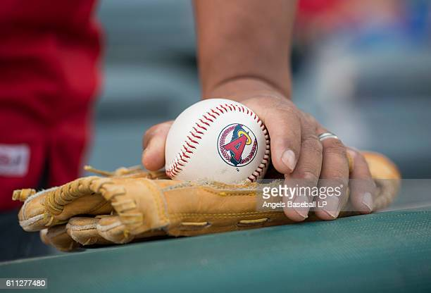 A detailed view of a fan holding a baseball with a 1980's era California Angels logo before the game between the Oakland Athletics and the Los...